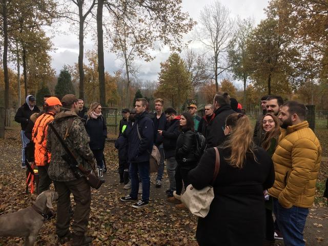 Schüler*innen stehen zusammen und hören den Berichten der Jäger zu.